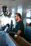 Deck crewmember Dennis Brooks serves as helmsman.