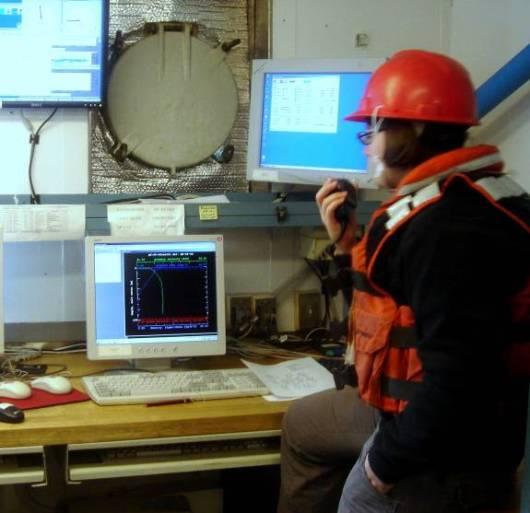 Survey Technician Tayler Wilkins monitors the CTD data transmission while communicating with the crane operator as the rosette is lowered through the water column. The computer automatically produces a profile of temperature and salinity with depth.