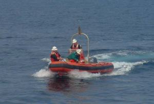 """Rescue crew retrieves a dummy man overboard. It is a maritime custom to refer to the man overboard as """"Oscar."""" This comes from an international regulation requiring the raising of the Oscar flag when a vessel is responding to a man overboard, warning other vessels to be on the lookout"""