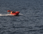 Orange rescue boat speeding along the ocean's surface