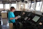 Sue standing at the console on the bridge taking notes