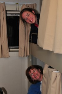 Jana peeking out from curtains in top bunk Sue peeking out from bottom bunk