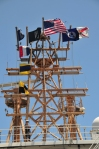 Intricate mast with American flag in center, 4 flags flying vertically, the NOAA flag, and AL state flag