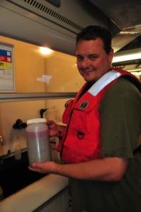 Steve in PFD holding container with sediment and pink color