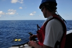 Dave in a blue helmet and orange PFD standing outside with a joystick with the ROV in the distance