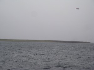 A helicopter leaves the airport on 27 June. That spit of land is the runway.