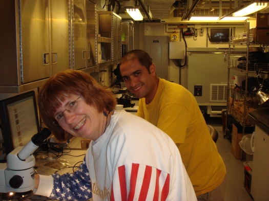 Sue in sweatshirt looking up from microscope. Diego in the background.