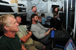 Men watching computer screens in control room piloting the ROV