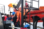 The victim, a dummy in orange, is brought aboard