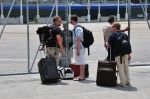 Men exiting a gate with suitcases