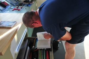 Captain leaning over filing cabinet referring to book