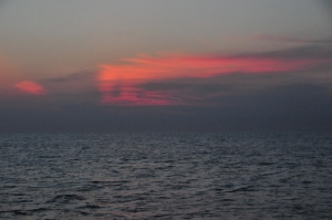 Red sunset within clouds over the ocean