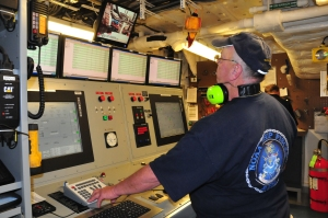 Chief engineer standing at large console watching gauges