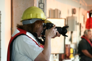 Sue in yellow helmet and orange PFD taking photograph with long lens