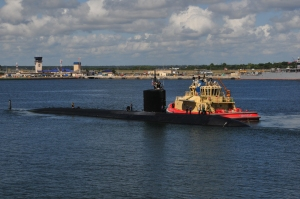 Black submarine next to an orange tug in the center of the harbor
