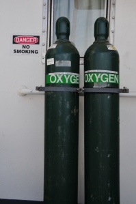 Two green oxygen tanks strapped to wall