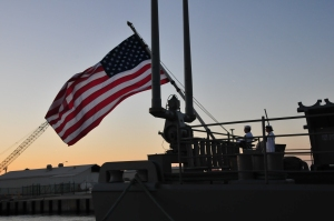US flag unfurled off back of ship at sunset