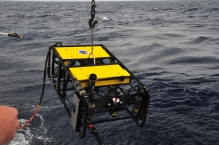 ROV hanging from a cable being lowered into the water.