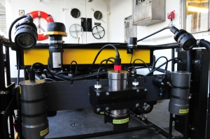 Front of ROV with headlights peering down.  Lots of black tubing and a yellow rectagle.