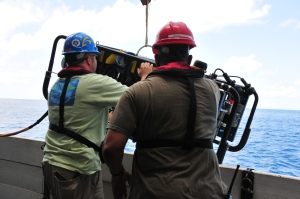 Two men with helmets holding the ROV over the side of the boat, helped by a winch.