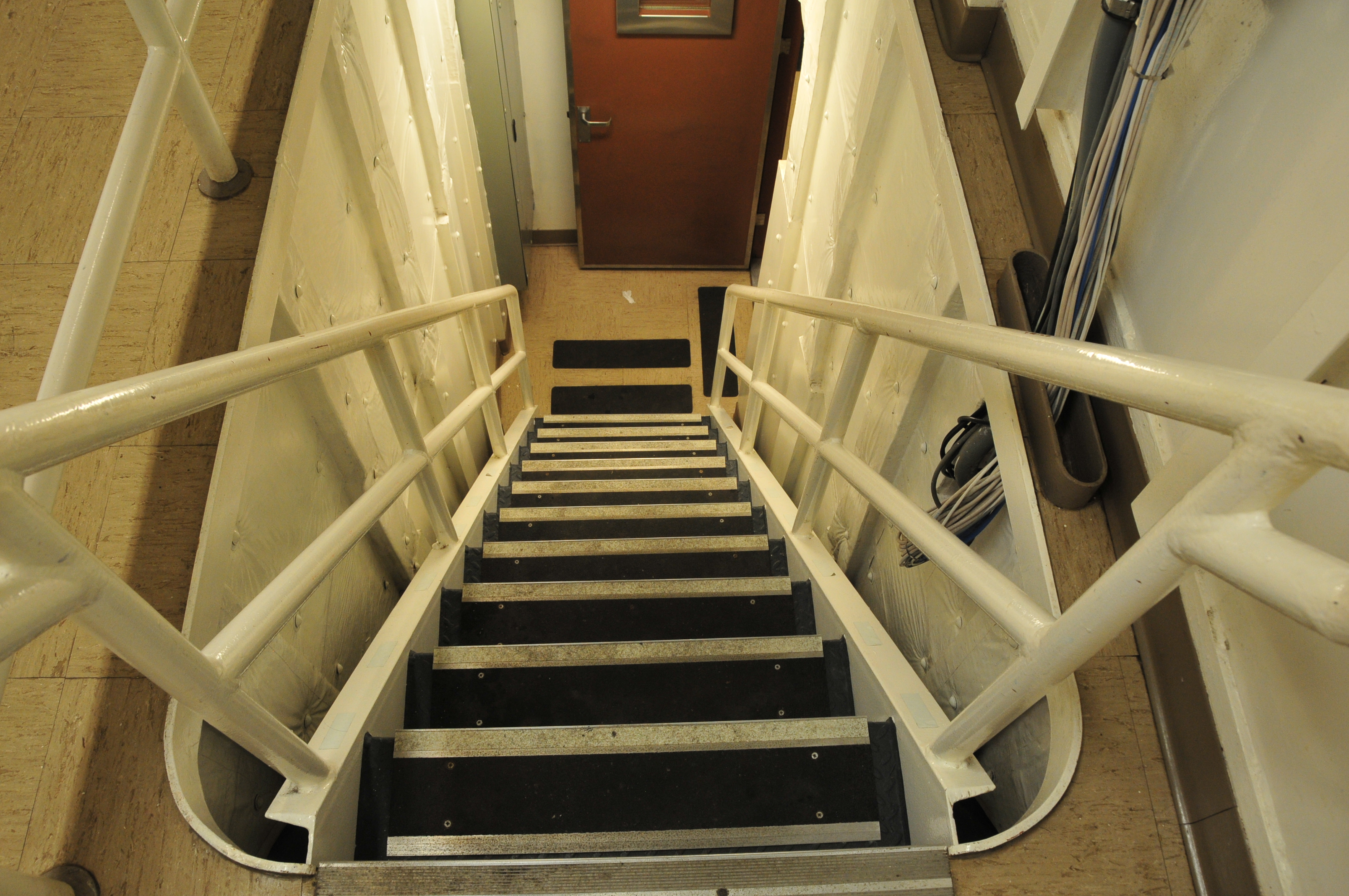 Looking Down Stairwell With White Railings And Black Steps. Steep Stairs
