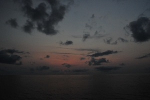 Sunrise over the ocean; dark sky, puffy clouds, pink horizon
