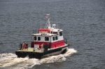 Red and white tugboat with a white waves around it