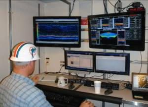 "Acoustics team leader Warren Mitchell examines sonar display. Miami Dolphins ""thinking cap"": optional."