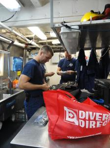 NOAA Ship Nancy Foster officers ENS Jamie Park, ENS Michael Doig and Lt Josh Slater (hidden), inspect diving equipment.