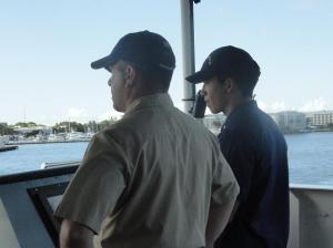 Ensign Richard De Triquet  (right) maneuvers the ship. Executive Officer CM Donn Pratt (left) observes.