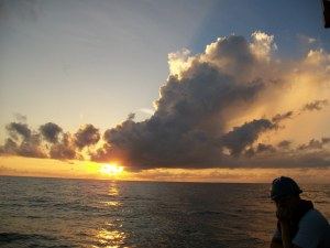 Christian Jones, an NOAA employee, is admiring a sunset off the stern of the Delaware II.