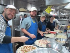 Erin Clark, USGS engineering technicians Jenny White and Pete dalFerro, and USGS geochemist Chris Dufore (pictured from right to left) put their skills to the test with an efficient assembly line, combining toppings for a diverse array of pizza choices. Photo courtesy of Helen Gibbons.