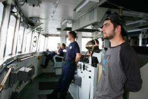 Commander Mike Hopkins, LTjg Oliver Brown, and crewmember John Adams conduct a marine mammal watch on the bridge before a fishing trawl.