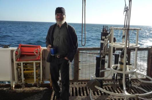 Dr. Steve Pierce  at his work station and standing next to the CTD on a bright sunny day in the Northern Pacific Ocean.
