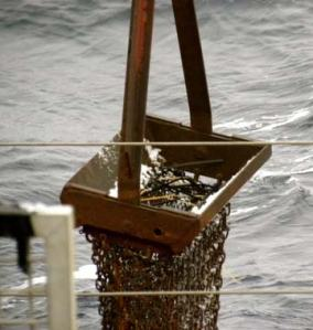 The empty dredge being lowered into the ocean.