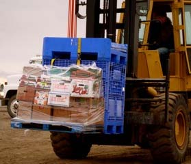 A forklift carries food supplies to the Healy
