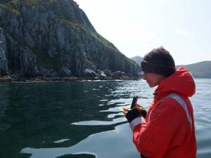 Taking a compass bearing for a previously uncharted danger to navigation.  The rock found is only visible at low tide which makes it all the more hazardous.