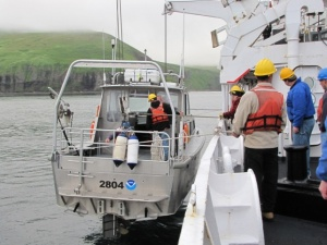 This is a survey launch lowered to deck level on a calm day. The bow and stern are attached to the davits by thick line.  Notice how you have to step across the space between Rainier and the launch.