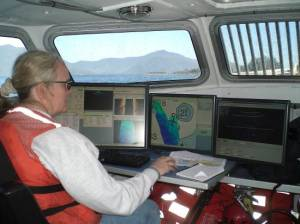 Here I am working the sonar on a launch. Computer screens showing a vast array of data being collected and the charts used to record the data.
