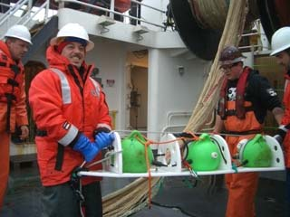 """Roy works with the deck crew to remove the """"pea pod"""" from the trawl net."""