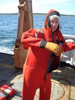 Becky dons her survival suit during a safety drill.