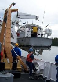 Crew of the NOAA Ship RAINIER prepare to deploy a launch.
