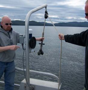 "Survey technicians Shawn Gendron and Matt Boles are retrieving the ""grab"" from sampling the bottom."