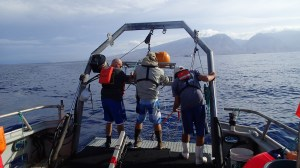 Chris Demarke, Jamie Barlow, and Bo Alexander retrieving a BotCam aboard the Huki Pono with Maui in the background