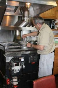 Bill, the Chief Steward of the JOHN N. COBB, cooks a delicious dinner for the crew.