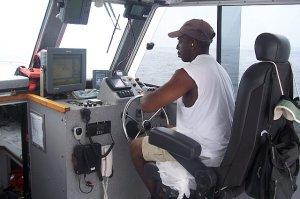"""One of the jobs on the ship is coxswain, or """"cox'n.""""  Here, Cox'n Pooser drives a launch."""