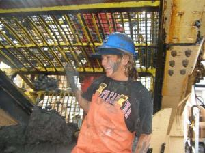 Lisha in the clam dredge towing out the dark, clay sediment.