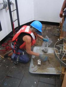 Lisha collecting the sediment sample that was hauled in by the bottom grab.