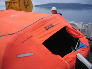 Chief Boatswain, Jim Kruger, demonstrates a life raft in a session aboard the RAINIER.