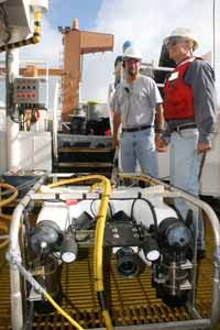 ROV team Lance Horn (left) and Glenn Taylor prepare the ROV for deployment.